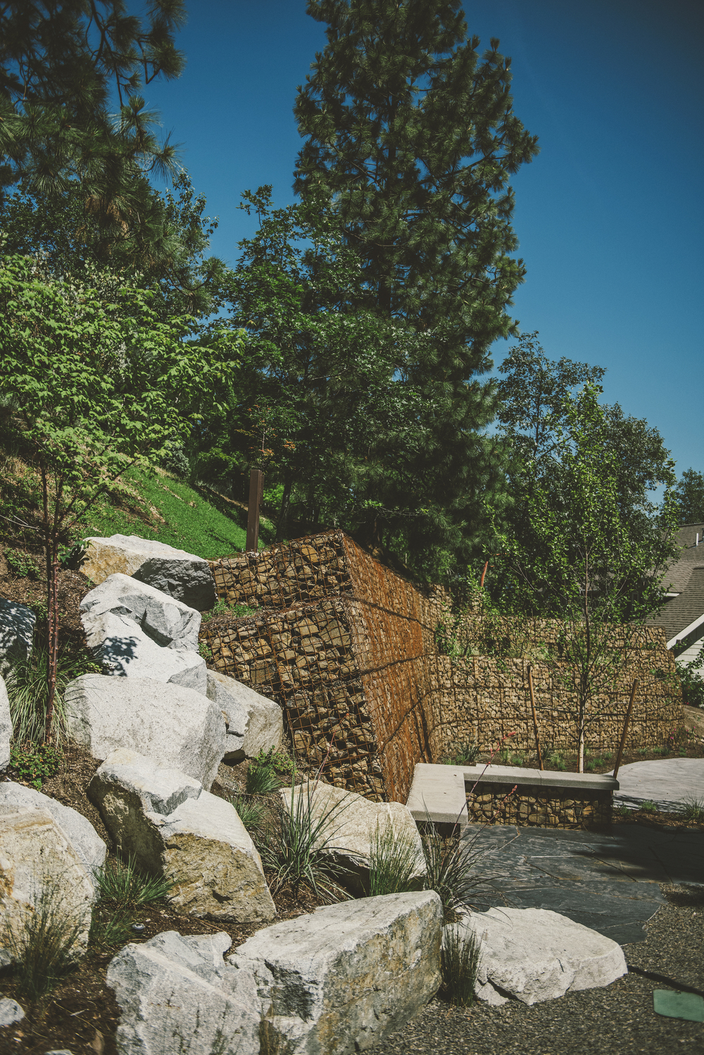 Erosion Control Design. Gabion retaining wall with concrete + gabion bench and granite boulder hillside.jpg