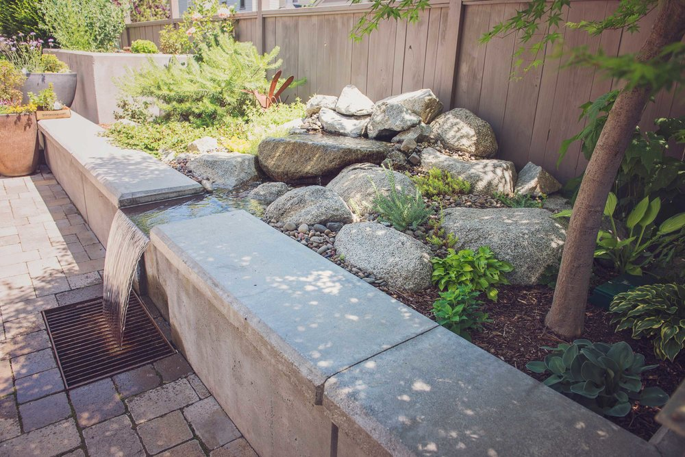 Formed concrete water feature + modern steel grate + concrete slab outdoor seating + brick paver patio + corten planter + granite boulder + river rock water feature