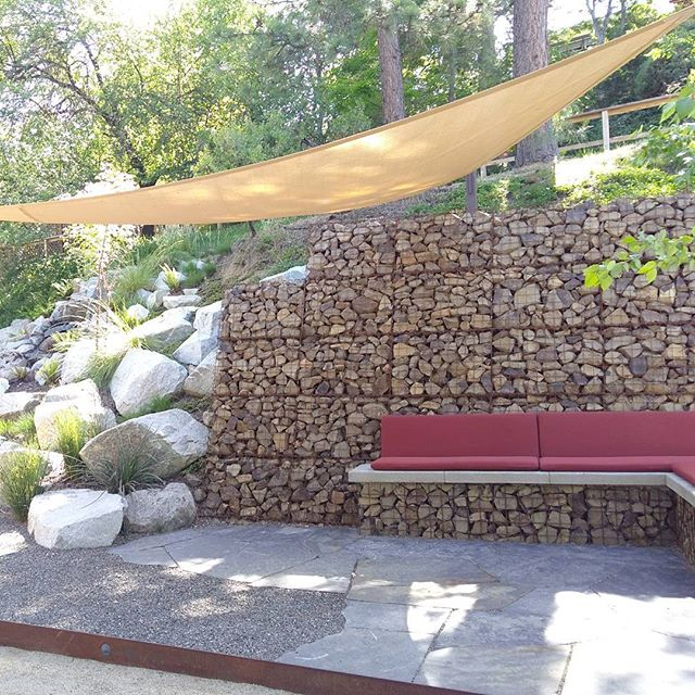 The shade sails are up! This inviting bench has a great view of the bocce ball court and the boulder creek water feature. Designed and installed by Regenesis. #shadesails #gabion #flagstone #nativeplants #chillout