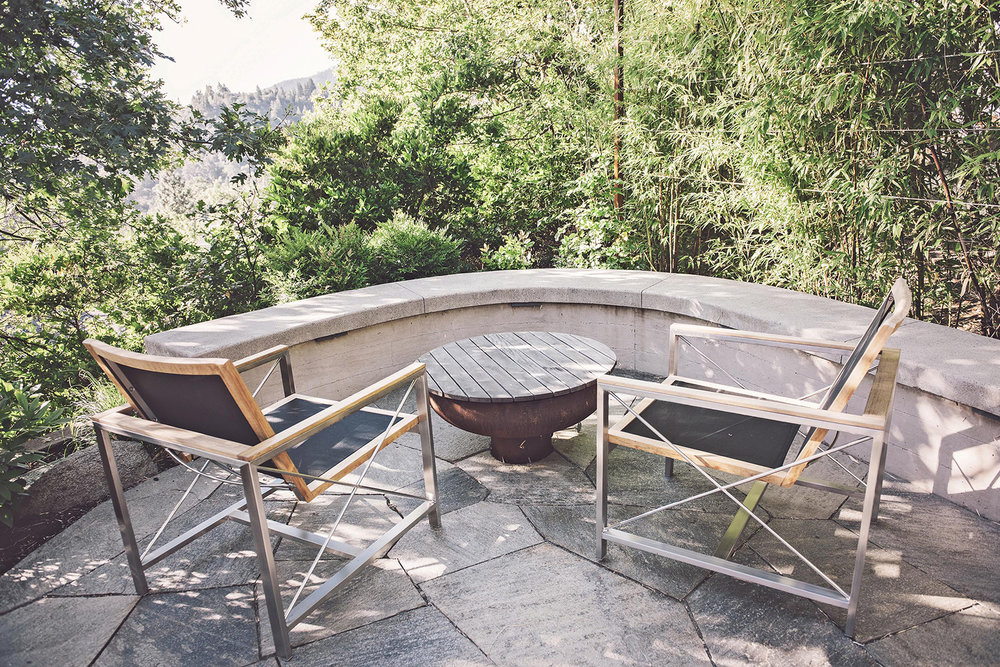 outdoor patio view + flagstone patio + corten fire bowl + wood cover + modern seating area + curved concrete bench seat.jpg