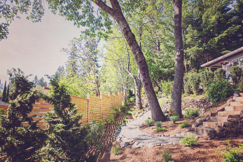 Horizontal Slat Fence +Timber Stair + crushed basalt gravel path + white oak backyard grove + perennial plantings + hillside landscaping + cobble retaining walls.jpg