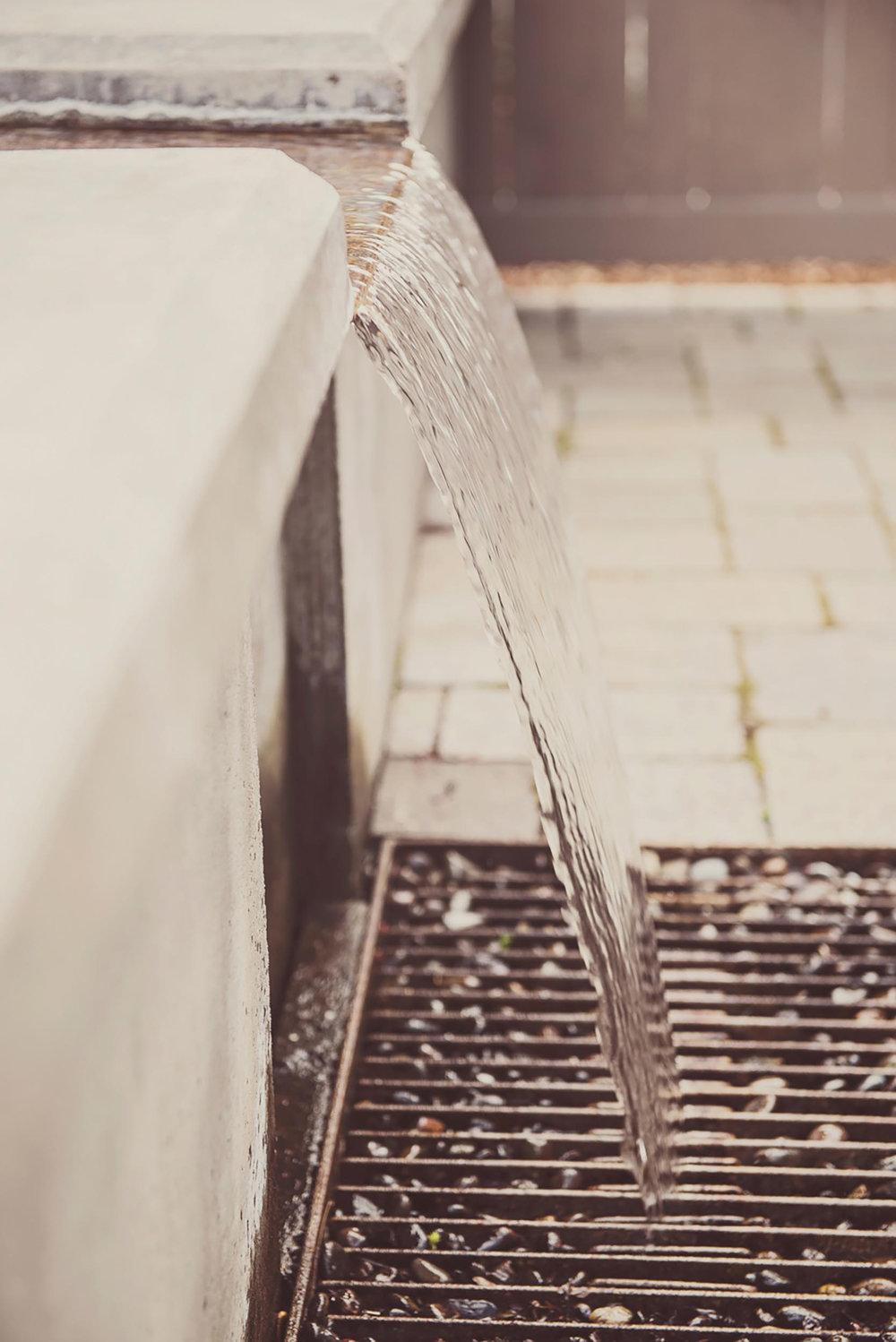 pour over modern water feature + steel grate + concrete bench slab