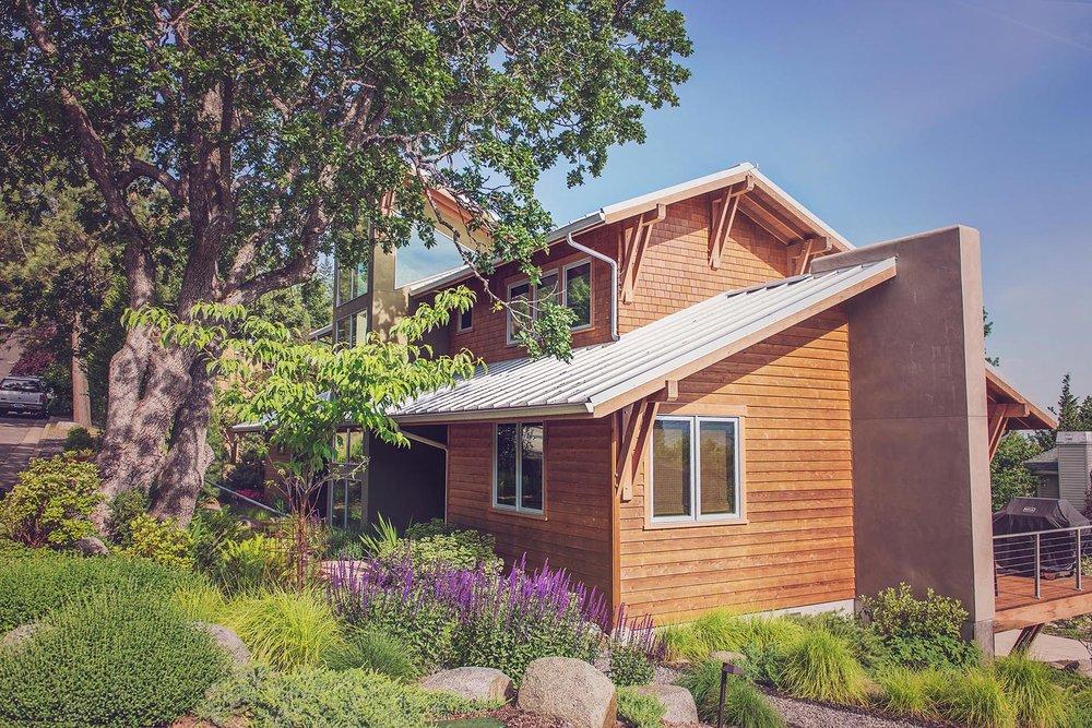 Large oak tree + perennial garden + placed granite buolders + autumn moore grass + salvia + rhododenron +