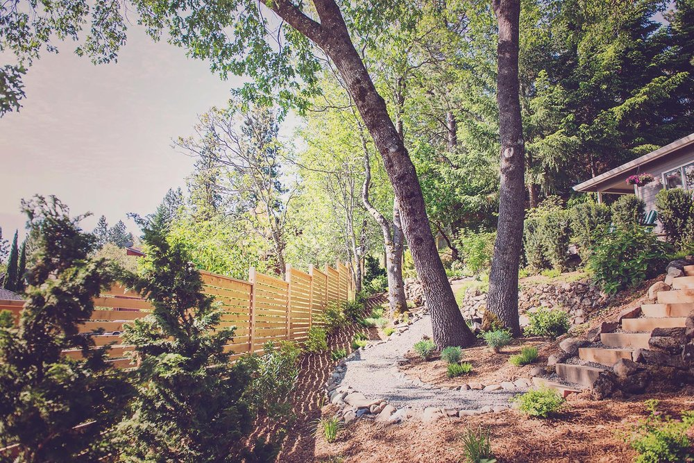 Horizontal Slat Fence +Timber Stair + crushed basalt gravel path + white oak backyard grove + perennial plantings + hillside landscaping + cobble ret