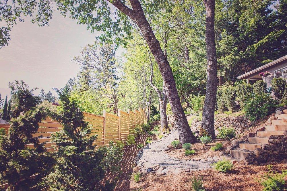 Horizontal Slat Fence +Timber Stair + crushed basalt gravel path + white oak backyard grove + perennial plantings + hillside landscaping + cobble ret