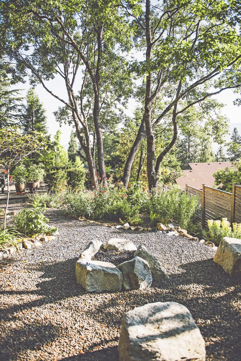 granite boulder fire pit + crushed basalt gravel paths + locally quarried rock + colorful perennial flower garden + oak canopy + modern slatted priva