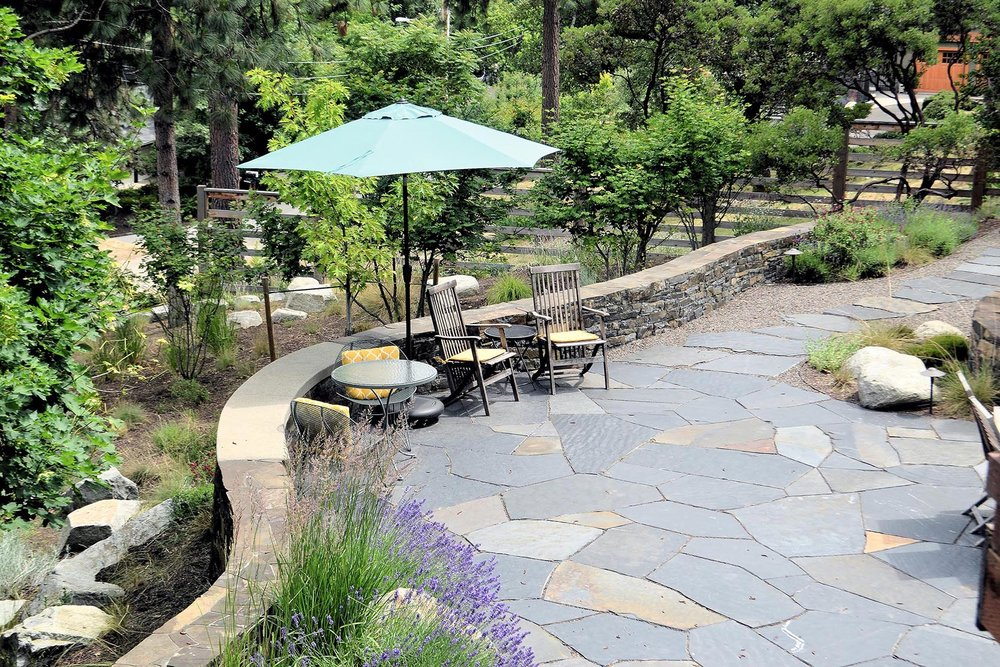 Flagstone Patio with Chairs and Umbrella and Built-in Stacked Stone Seating Wall