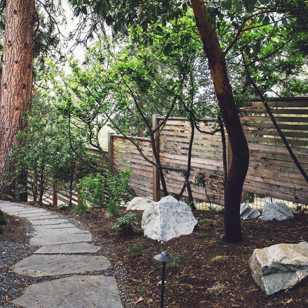 forest path + flagstone stepping stones + local crushed basalt gravel + placed grabite boulder garden + low profile landscape lighting + horizontal
