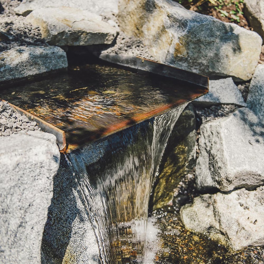 natural + built water feature + pour over + rusted steel + granite boulders j+ crushed basalt gravel + modern PNW boulder