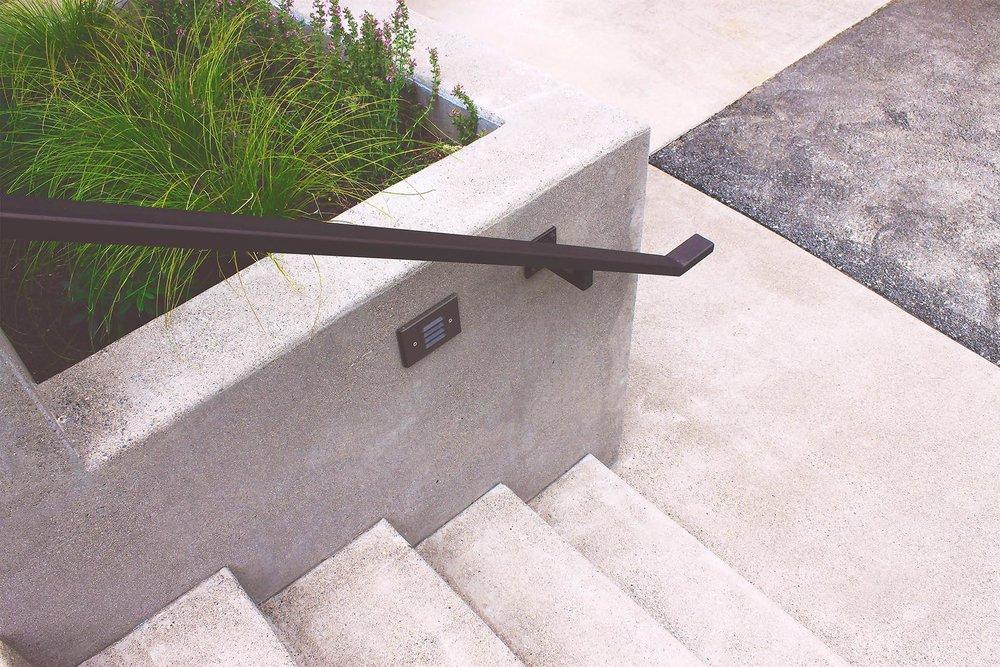 Concrete Stairway Entrance + Custom Steel Railing + Low-profile landscape lighting + Terraced Concrete Planters + Modern