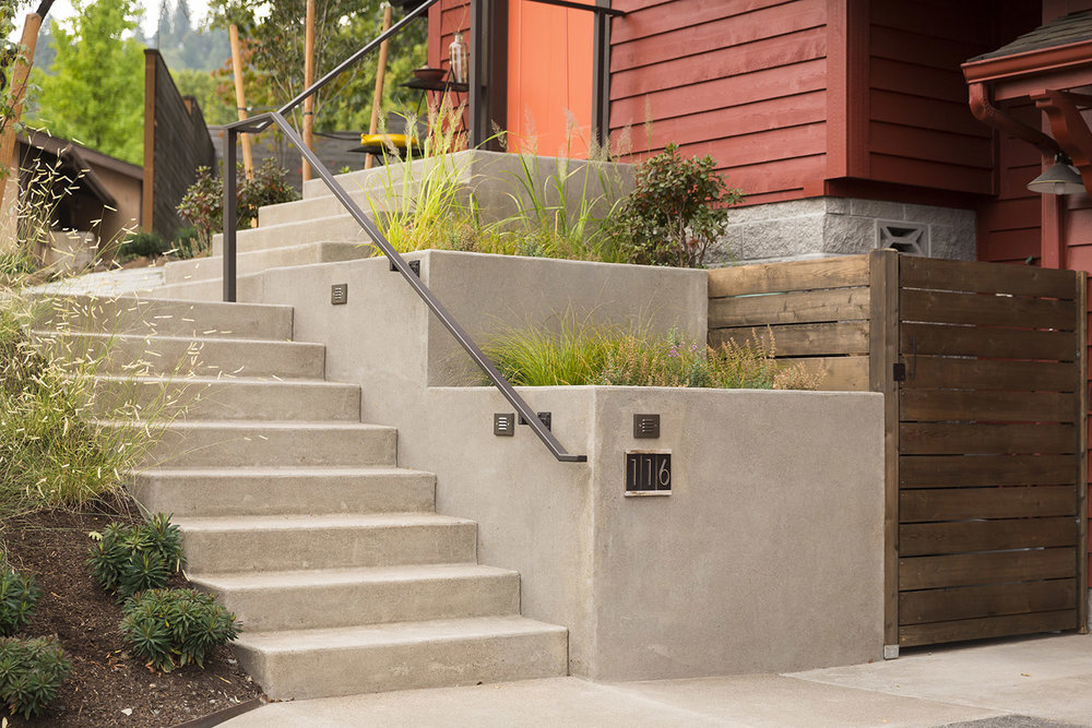 Sand-finished concrete entryway + steel handrail