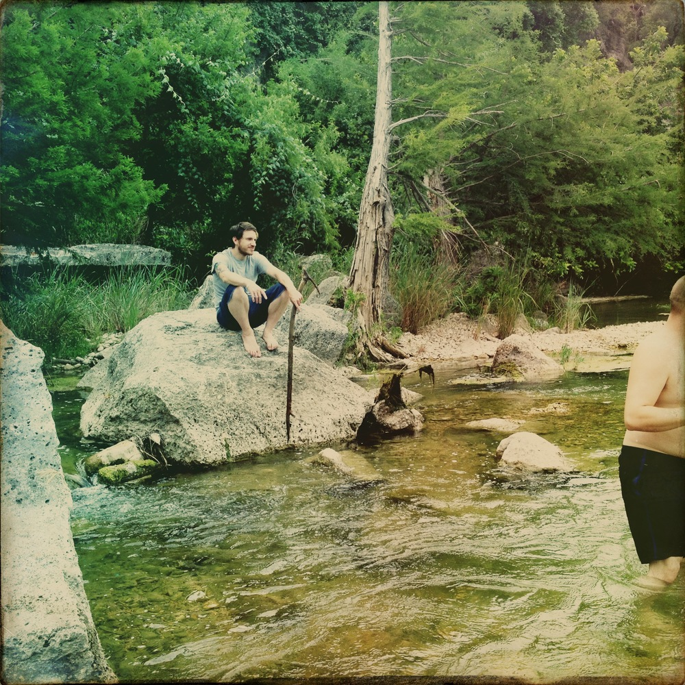 James sitting on a rock in the river