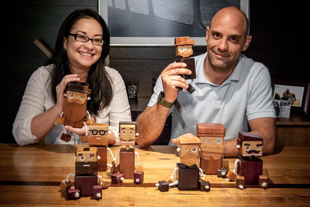 Lu Mori, curadora no blog Ateliê Criativo, e André Pedrini com os 8 bonecos de madeira da coleção Toy art(ists).