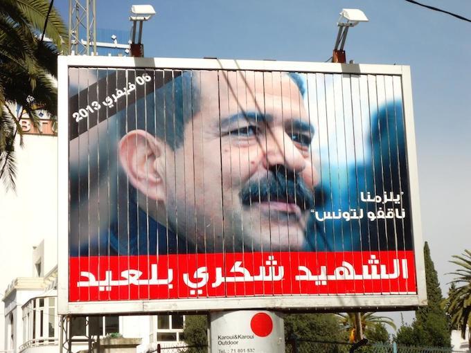 """Un panneau publicitaire commémorant le """"Chahid"""" Chokri belaïed et la date de son assassinat."""