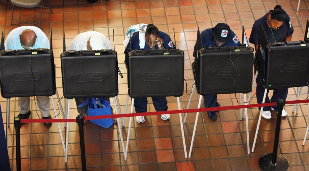 Des gens inscrivant leur vote dans un bureau de vote installé au Government Center dans le comté de Miami-Dade, le 8 octobre 2010, Miami, Floride. Photo : Joe Raedle/Getty Images