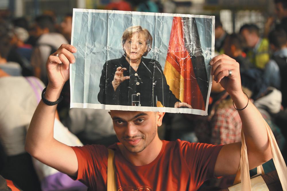 Un réfugié syrien tenant une photo de la chancelière allemande Angela Merkel lors de son arrivée à Munich avec des centaines d'autres migrants en provenance de Hongrie, en septembre 2015. Sean Gallup/Getty Images