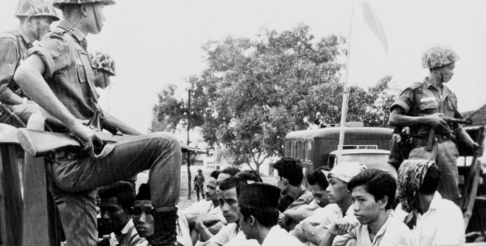 In this Oct. 30, 1965, file photo, members of the Youth Wing of the Indonesian Communist Party (Pemuda Rakjat) are guarded by soldiers as they are taken by open truck to prison in Jakarta. (AP Photo/File)