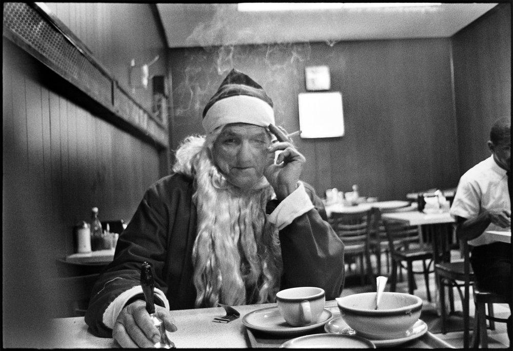 Photo Mary Ellen Mark, 1963.    Voir notre article.    Cette photo, prise en 1963, c'est on ne peut plus ça. Derrière l'image joufflue, bon vivant, généreuse, du père Noël, depuis des décennies, la réalité des pauvres hères, qui gagnaient quelques sous, quelques jours, en gelant devant des magasins, en espérant ne pas faire peur aux enfants. Cela ne se fait plus de nos jours. Personne ne croit plus au père Noël. Über Noël et son traîneau Amazon ont pris sa place. Et c'est d'une certaine tristesse, aussi. Autant que cette désarmante photo de l'envers du décor. Et même un peu plus.