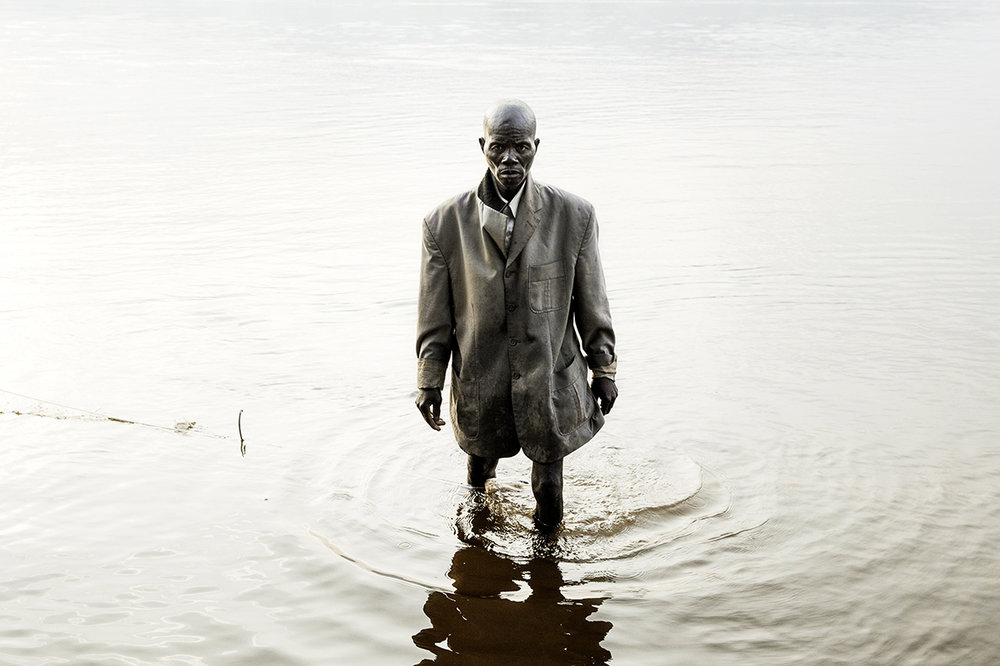 Centrafrique, 2014. Un homme habillé pour la messe dominicale marche dans la rivière Oubangui, tôt le matin. Avant d'exister en tant qu'État, la Centrafrique était considérée comme la « colonie poubelle » de l'Empire colonial français, qui a fermé les yeux sur le travail forcé jusque dans les années 1930. Ses frontières ont été tracées au mépris de toute logique géographique et ethnique. Le pays a connu cinq coups d'État et échappé de peu à un génocide. © William Daniels