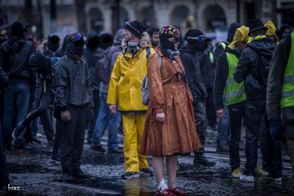 """Paris acte XVII - Prêts pour """"Singing In The Rain"""" sous le déluge des canons à eau. Encore un moment magique saisi par   Bsaz   (allez voir son portfolio sur  sa page Facebook  !), la photographe essentielle du mouvement des gilets jaunes."""