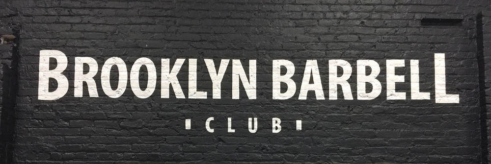 Sign on a brick interior wall in Williamsburg, Brooklyn for Brooklyn Barbell Club.