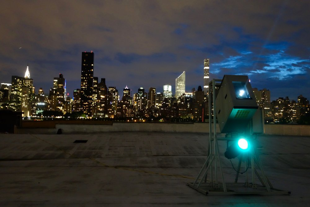 The video and static light projection rig on the rooftop with the Manhattan skyline in the background.