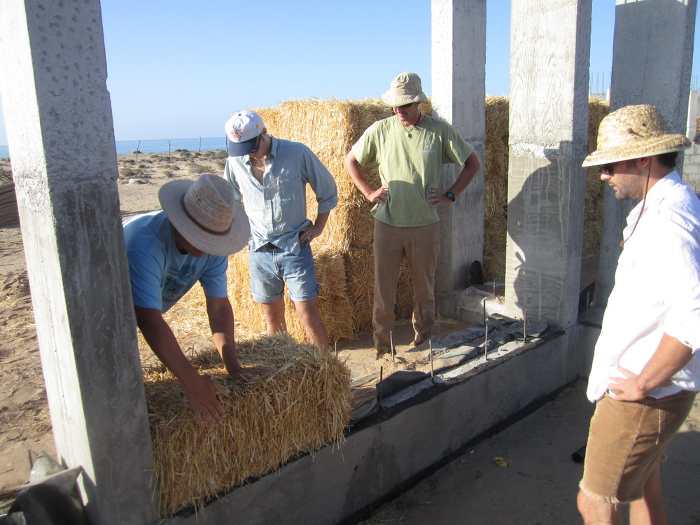 Dave Steibel is showing Griff Goins, Jim Greenleaf and crew member Ben Young how to place the bales.