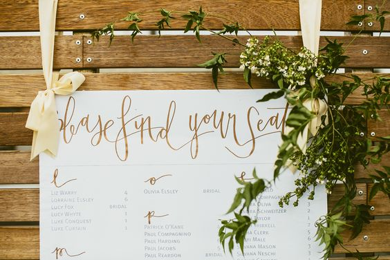 A refined, modern take on the regular seating chart. Gorgeous ribbon, copper hand-lettered script and beautiful greenery makes this a diverse look for many occasions.  Georgeous Occasions