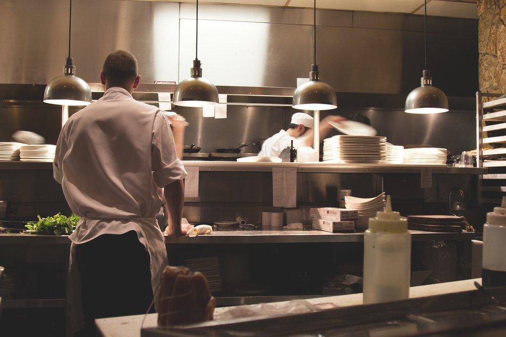 Chefs in restaurant kitchen cooking food