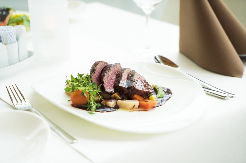 Steak dish at fancy restaurant with white tablecloth