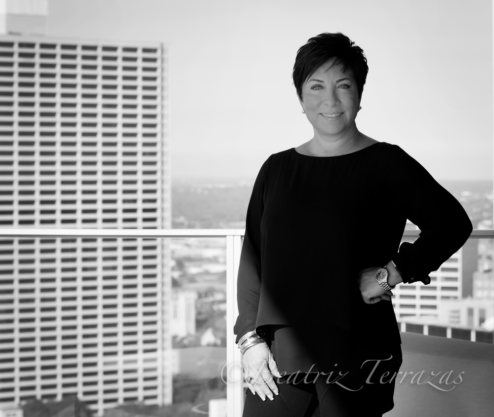 Sandra, on the balcony of her 27th floor condo in downtown Fort Worth. Owning a roofing company means you can't be afraid of heights.
