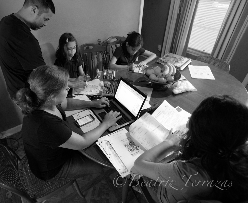 The Salinas family after school, with Sandra putting in volunteer hours and her husband Jaime helping the girls with their homework.