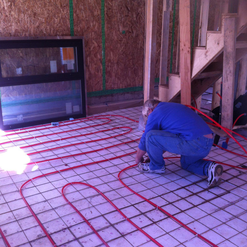 Installing radiant-floor heating pipes prior to the ground floor concrete slab being poured.