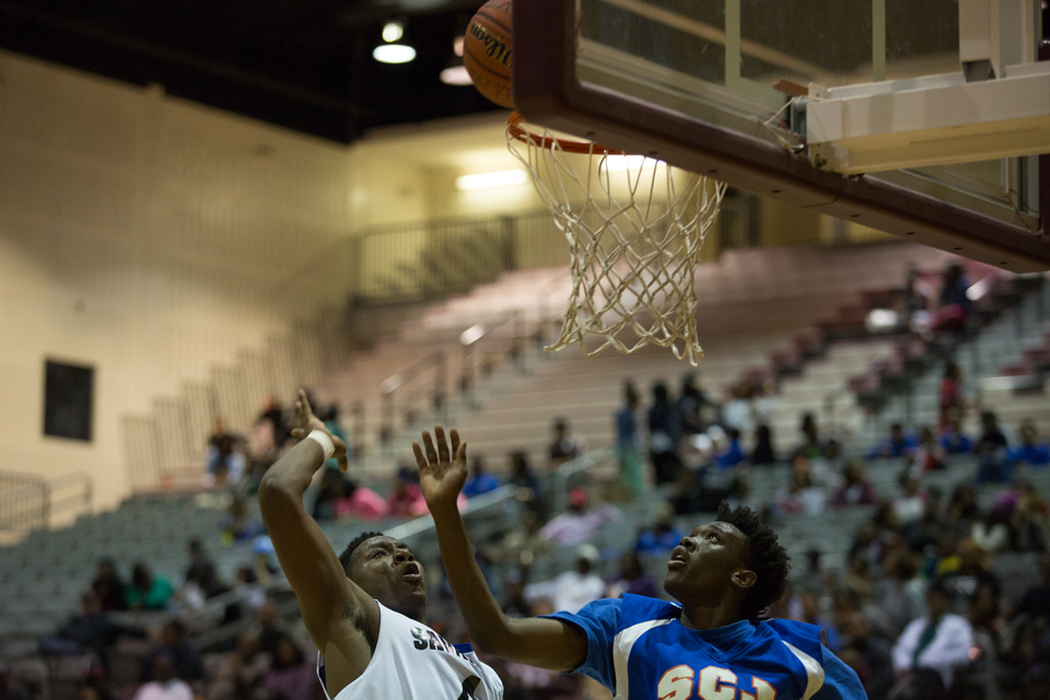 Joshua Galemore for Savannah Morning News - Savannah High player, Jermaine Williams (left), attempts to make a basket as Raquan Green (right), from Johnson, tries to block him.