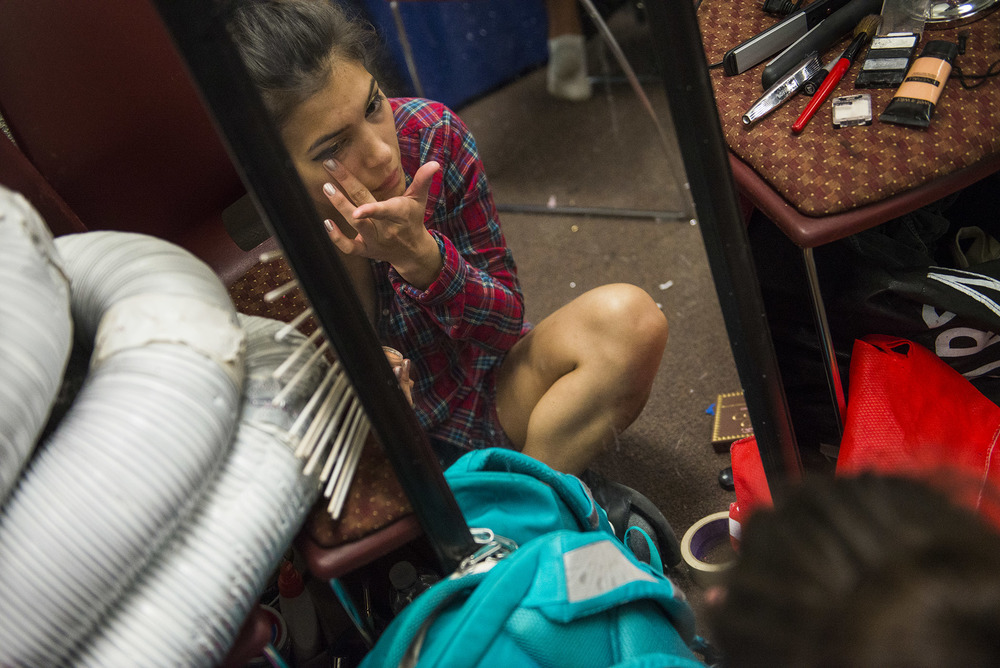 Alejandra Rivera, a student model for Junk2Funk, wipes away a bit of eye-liner while preparing for the Saturday matinee at Savannah Arts Academy.