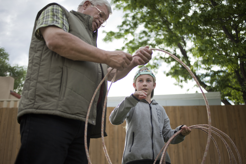 Mel Ashland teaches his granddaughter Carmel how to use a lasso during Western Night at the Philmont Training Center.