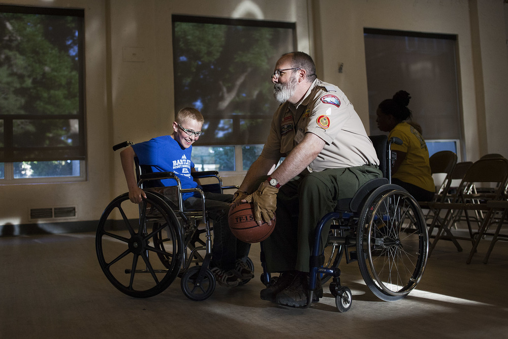 Scott Hellen (right), from Boston Massachusetts, plays wheelchair basketball with a boy at The Philmont Training Center during a disability obstacle course. Hellen has been unable to walk without assistance of a wheelchair or crutches for 17 years but still stays active riding his rowing bike and hiking with his local Boy Scout Troop. The event was put on at PTC in order to raise awareness about how it is to live with a disability in hopes that it will lead to councels focusing more on accommodating their own scouts with disabilities.