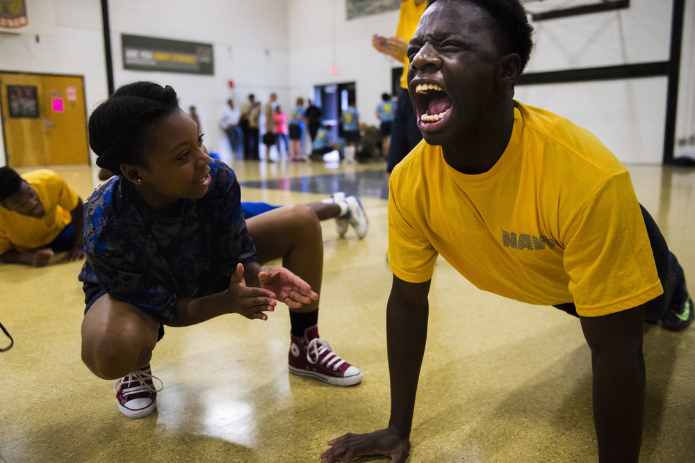 Julica Weikerson cheers for fellow Johnson High School cadet LeRoy Alexander as he does pushups during JROTC competitions held at Groves High School.