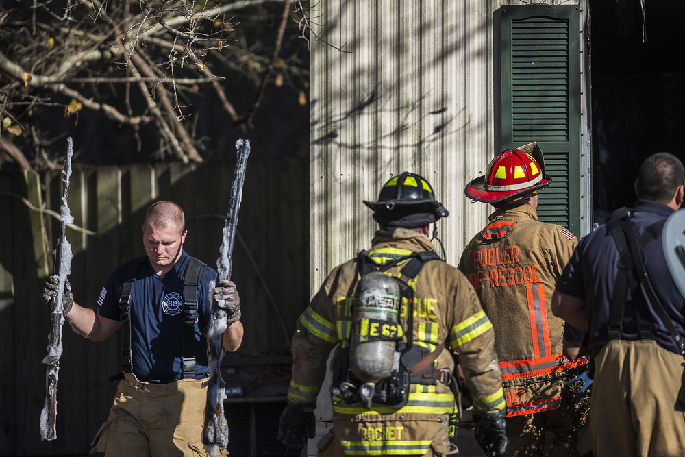 A Pooler Firefighter carries two rifles from the burnt out mobile home on Gina Circle. When emergency personnel arrived at the scene the owner of the home was still inside and gunshots were heard going off due ammunition being exposed to extreme heat. There were over 50 guns taken from the residency after the fire was controlled.