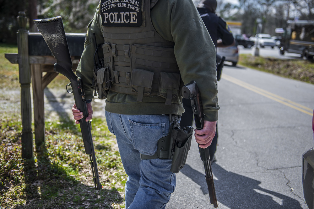 A U.S. Marshal carries a rifle and shotgun that were found in a house of a convicted felon during a raid for a suspected fugitive who the team thought was staying at the house.