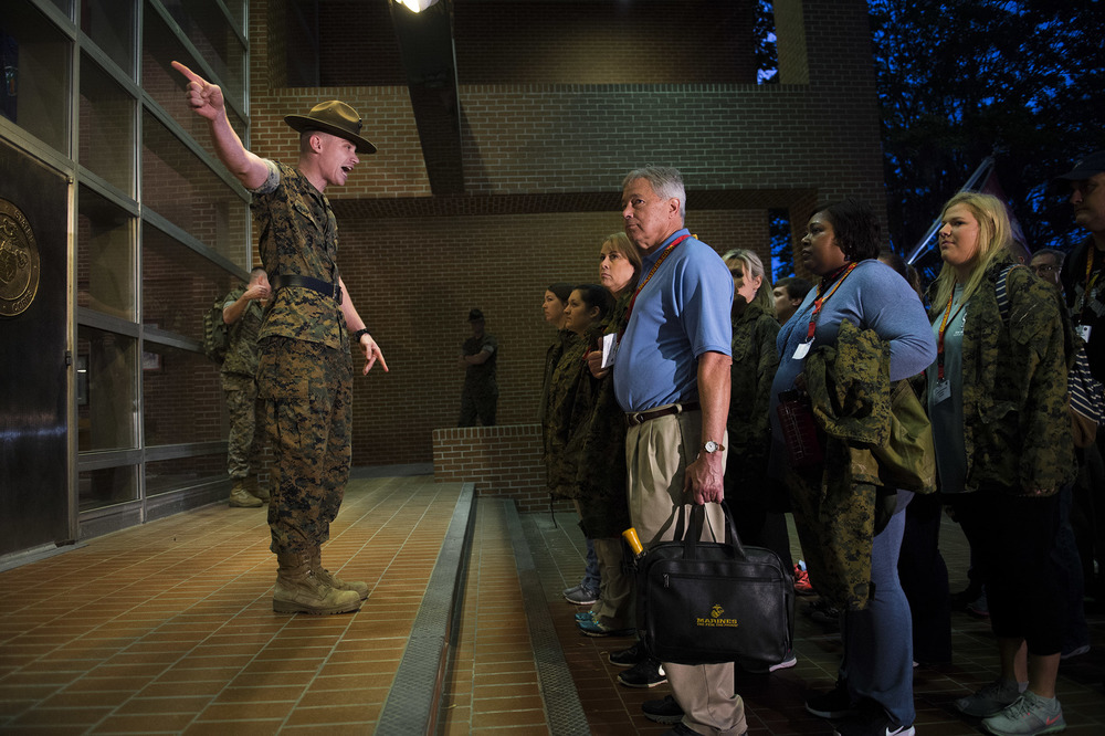A Drill Instructor gives direction on which hatches teachers from Jacksonville (FL), Montgomery (AL), and Savannah, should enter the Recruit Receiving Building upon their arrival to Parris Island for an educators workshop with the Marine Corps.
