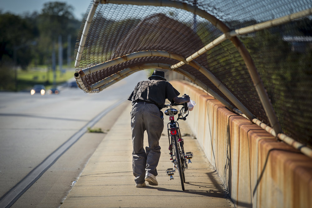 A man walks his bike under a fence on Bay Street which was bent from heavy winds caused by Hurricane Matthew.