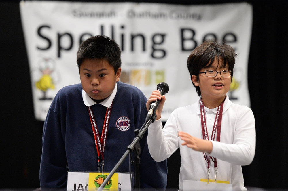 "Gio Ramos makes a face after forgetting an ""l"" while attempting to spell ""millennium"" as Garrison student Bryan Jung Kim takes the mic in attempt to spell the final word of the Savannah-Chatham Spelling Bee. Kim won the bee with the word ""mustache."""