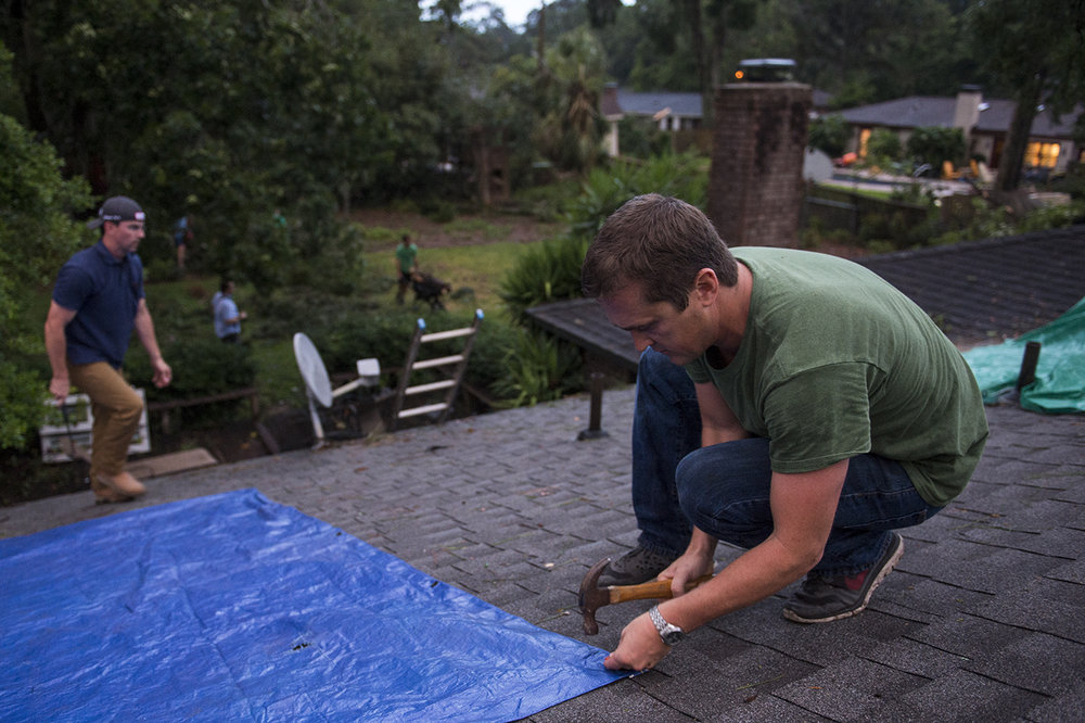 Hunter Saussy the IV hammers in nails to hold a tarp in place over a hole in his friend's roof on Wilmington Island after a severe storm passed through the area causing heavy damage to several houses.