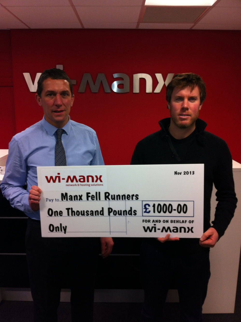 Manx Fell Runners club secretary David Griffin (left), pictured with Charlie Whipp of Wi-Manx Limited, receiving a cheque for £1000 as sponsorship of the 2014 Manx Fell Runners Fell League.