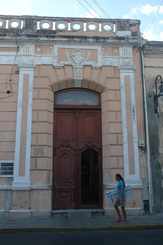 beige facade woman walking by.jpg