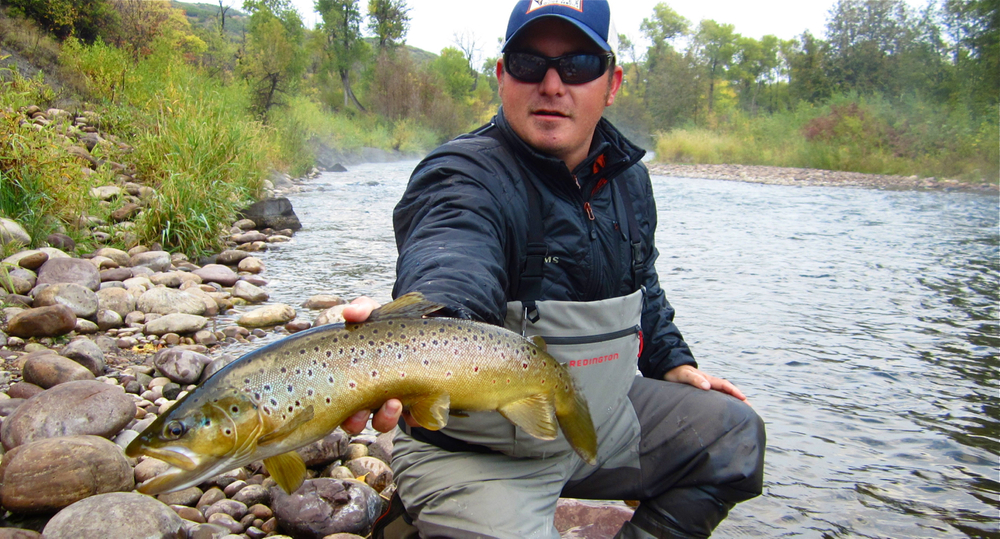 Jeff holding a nice brown trout caught by long time client, Jim.  Early morning, fall fly fishing in Utah