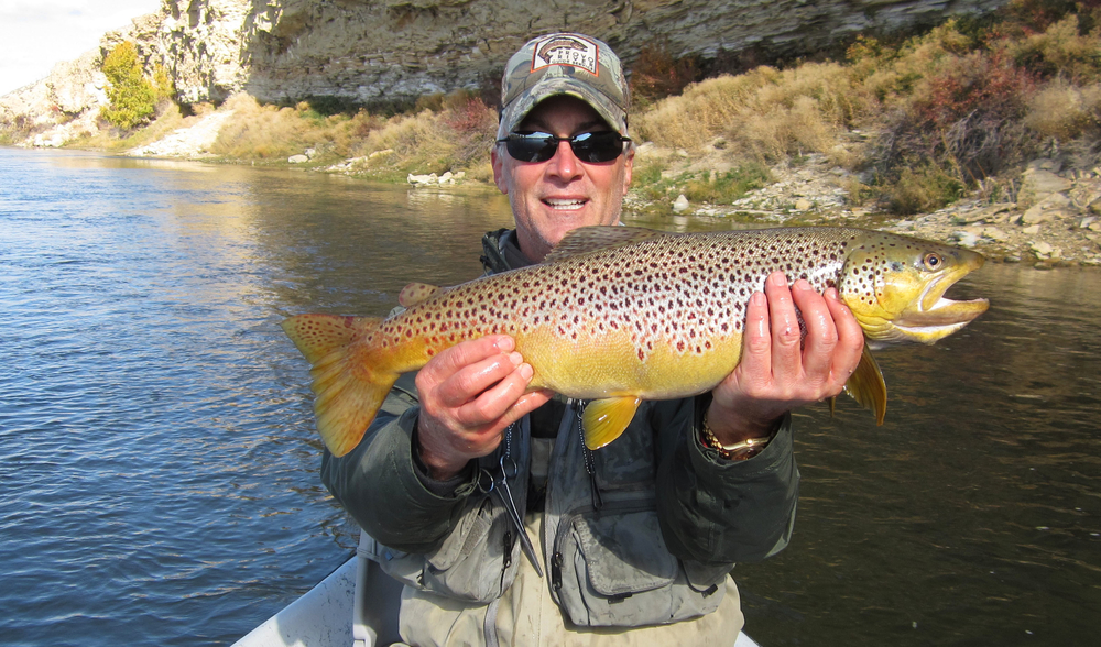 Jim with a brown trout, fly fishing in Wyoming