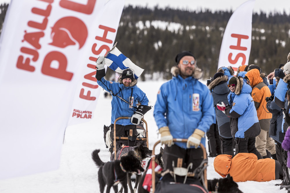 Fjällräven participant Tuomo Lampela waves the Finnish flag as he crosses the finish line at Lake Väkkeräjärvi. (Photo by Håkan Wike for Fjällräven International. All rights reserved.)