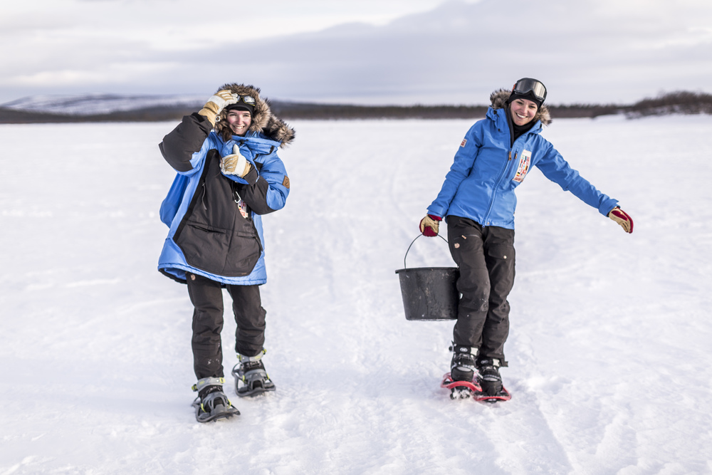 Fjällräven Polar participants Petra Obrovská (Czech Republic) and Katrina Sokk (Estonia) fulfill their camp duties —  in this case, fetching water to boil —  more successfully with the aid of snowshoes.  (Photo by Håkan Wike for Fjällräven International. All rights reserved.)